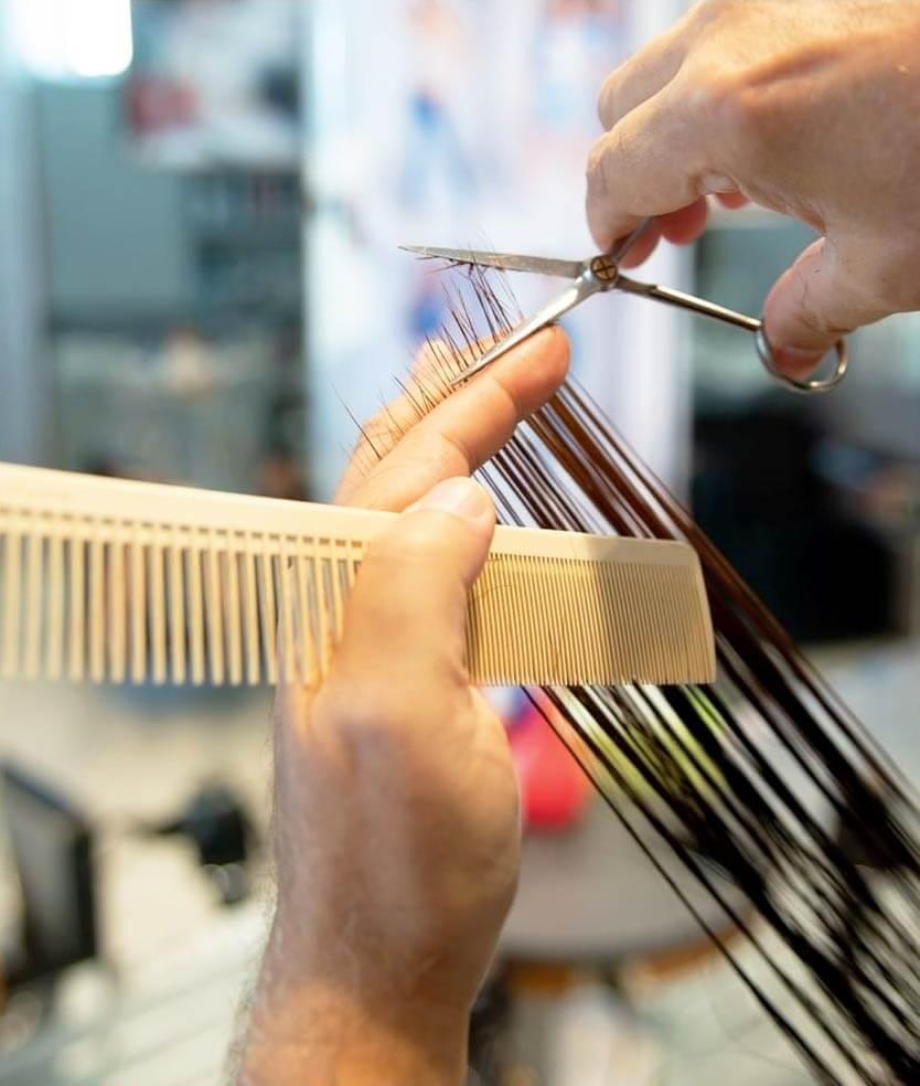 Parrucchiere al lavoro sulle punte dei capelli con forbici e pettine